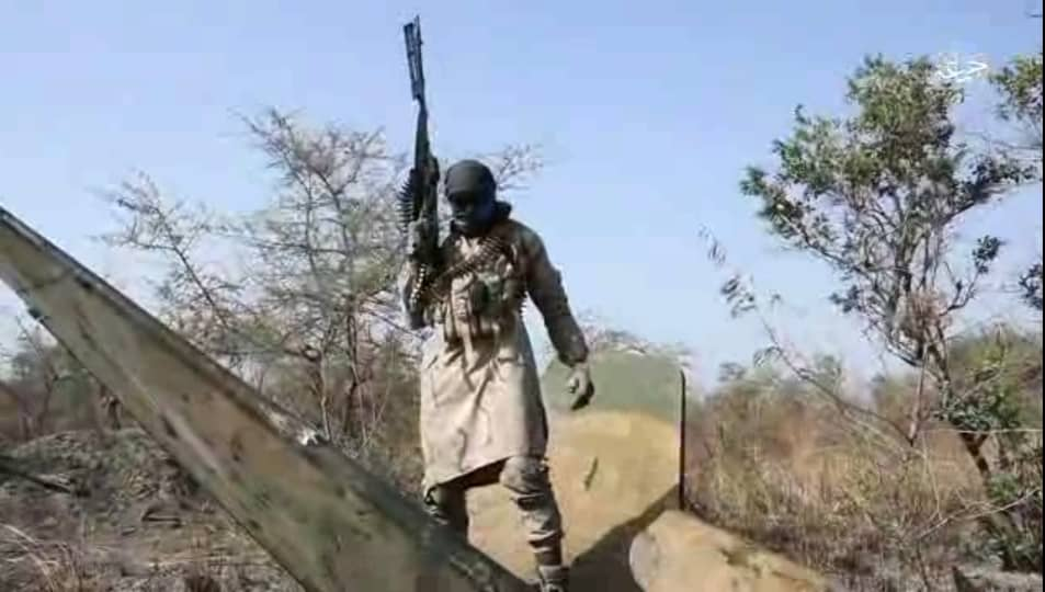 A Boko Haram fighter armed with a machine gun stands on the aircraft debris.